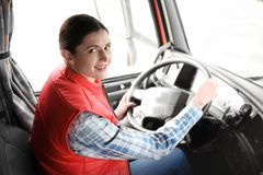 Young female driver sitting in cabin of big truck stock photo