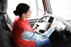 Young female driver sitting in cabin of big truck royalty free stock photos