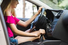Girl smile and learn how to drive. Young female driver on steering wheel with gear lever stock image