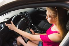Young female driver with tablet inside car royalty free stock image
