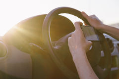 Young female driver using touch screen smartphone and gps navigation in a car. Stock Images