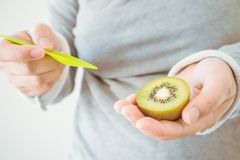 Female eating ripe kiwi fruit with wooden spoon. Young female eating ripe kiwi fruit with wooden spoon royalty free stock photo