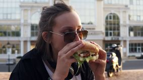Young female eats a big, juicy hamburger with two hands. Young girl with short hair and dark sunglasses. Hungry. Close. Up stock video footage