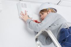 Young female electrician in hardhat climbing stepladder. Young female electrician in hardhat climbing the stepladder Stock Photos