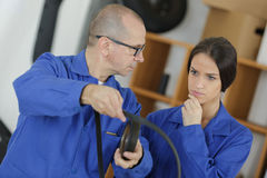 Young female electrician and mature electrician. A young female electrician and a mature electrician Stock Images