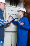 Young female electrician and mature electrician. A young female electrician and a mature electrician Royalty Free Stock Photos