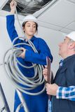 Young female electrician with mentor. Female Stock Photo