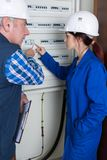 Young female electrician worker using fuse board. Young female electrician worker using a fuse board Stock Image