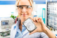 Young female electronic engineer holding HDD in hand royalty free stock photo