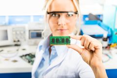 Young female electronic engineer holding memory module in hand Stock Photography