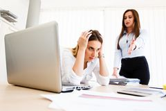 Young female employee has a lot of unsolved tasks. Angry boss - stressful day at work royalty free stock images