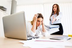 Young female employee has a lot of unsolved tasks. Angry boss - stressful day at work royalty free stock photography