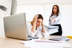 Young female employee has a lot of unsolved tasks. Angry boss - stressful day at work royalty free stock photos