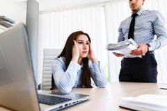 Young female employee has a lot of unsolved tasks. Angry boss - stressful day at work stock image