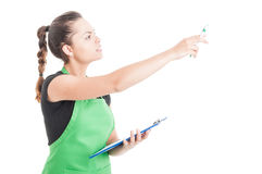 Young female employee holding clipboard and pointing finger Stock Photos