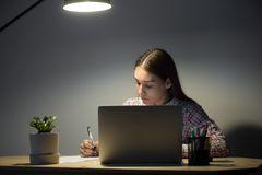 Young female employee read about last project and making notes. Royalty Free Stock Photos