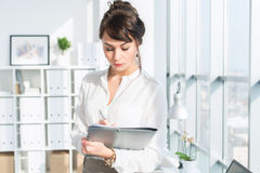 Young female employee, standing in office, wearing her work suit, reading business papers attentively, front view Royalty Free Stock Images
