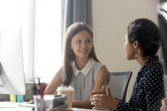 Young female employee talking with colleague at workplace stock images