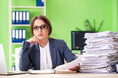 The young female employee very busy with ongoing paperwork stock photography