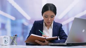 Young female employee writing in notebook, planning work day, ideas, discipline. Stock footage stock footage