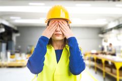 Young female engineer covering her eyes. As disappointed manager concept on indoor factory background Royalty Free Stock Photo
