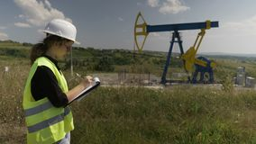 Young female engineer doing research near an oil pump unit noting information data on her clipboard -. Young female engineer doing research near an oil pump unit stock video