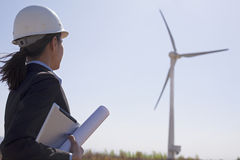 Young female engineer holding blueprints and checking wind turbines on site, Stock Photography