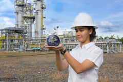 Young female engineer holding earth sphere. Royalty Free Stock Photos