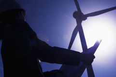 Young female engineer holding open blueprints and checking wind turbines on site, silhouette, low angle view Stock Images