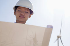 Young female engineer holding open and looking down at blueprints, on site with wind turbines Stock Images