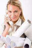 Young female engineer on phone carry blueprints Stock Photography