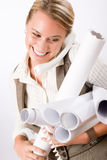 Young female engineer on phone carry blueprints Stock Photo