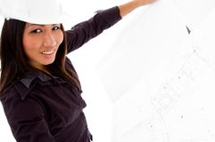 Young female engineer searching opened blue prints. Young female asian engineer holding opened blue prints against white background Stock Photo