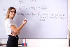 The young female english language teacher standing in front of the blackboard. Young female english language teacher standing in front of the blackboard stock photography