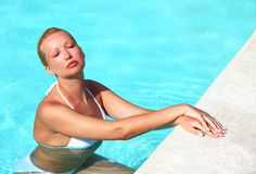 Young female enjoying sun in swimming pool Stock Photo