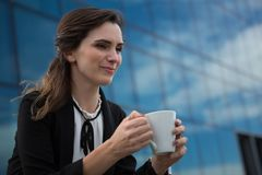 Female executive having coffee in office premises Royalty Free Stock Image