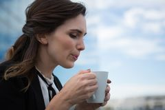 Female executive having coffee in office premises. Young female executive having coffee in office premises Stock Image