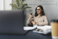 Free Young Female Executive Sitting At Workplace At Lunch Time And Listening To Music On Smartphone Using Earphones. Girl Using Mobile Stock Photography - 171989392