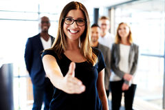 Young female executive standing with hand out Royalty Free Stock Images