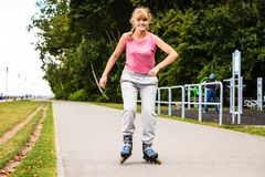 Young female exercise outdoor on rollerblades. Royalty Free Stock Photos