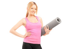 Young female with an exercising mat Royalty Free Stock Images