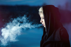 Young female exhaling smoke in black Stock Photos