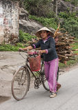Young female farmer walks bike loaded with fire wood. Royalty Free Stock Photo