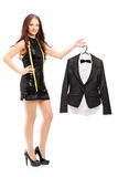 Young female fashion designer holding a bow tie suit on a hanger Stock Image