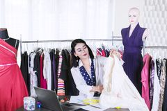 Young female fashion designer holds a fabric. Picture of young female fashion designer holding a fabric while sitting in the workplace stock photo
