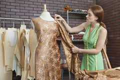 Young female fashion designer matching cloth with fabric draped on tailor's dummy Royalty Free Stock Images