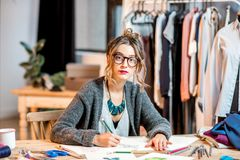 Fashion designer working at the office. Young female fashion designer sketching drawings of the clothes sitting at the beautiful office with different tailoring royalty free stock photos