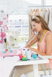 Young female fashion designer using phone Royalty Free Stock Photo