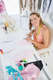 Young female fashion designer working on fabrics Stock Photos