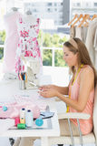 Young female fashion designer working on fabrics Stock Image